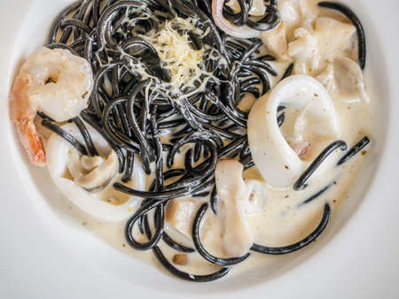Squid ink spaghetti seafood carbonara served on white plate. Closeup shot from top view Stock Photo