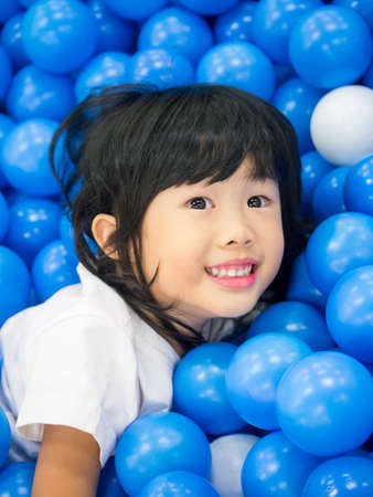Adorable asian child girl playing in the ball pool with cute smile