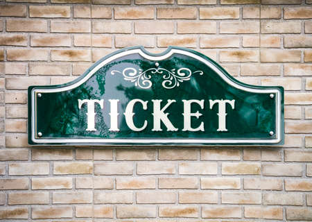 Green ticket sign on the brick wall