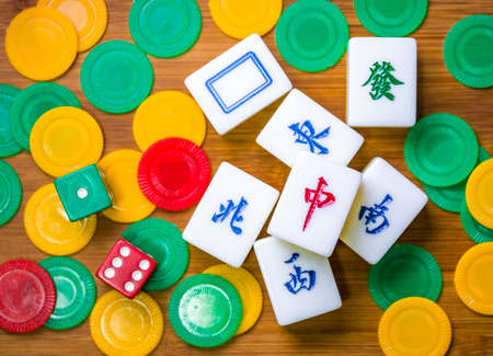 Mahjong, chips and dices scattered on the wooden table