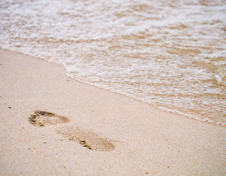 Human footprint on the beach in concept of travelling to the sea