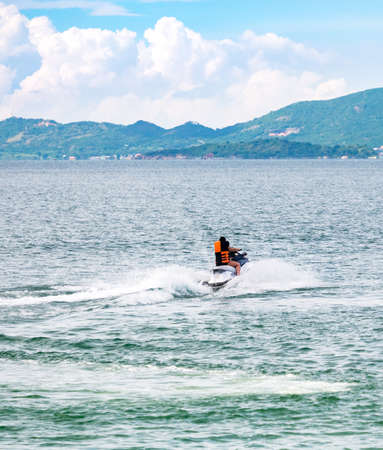 People riding jet ski in the peaceful sea Stock fotó