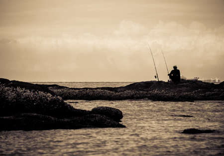 Silhouette of people fishing by the sea processed in sepia