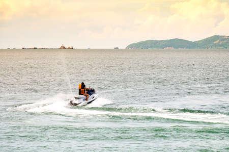 People riding jet ski in the peaceful sea Stock Photo