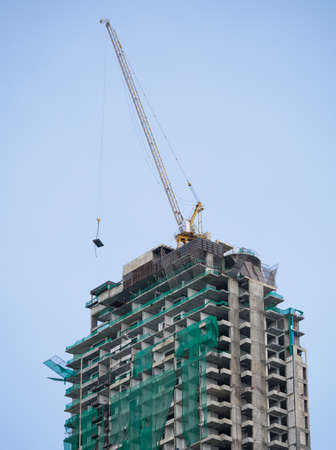 Under construction building with crane carrying the material up high