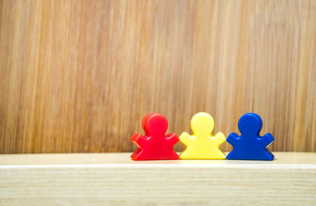 Three meeples on wooden background in concept of family game