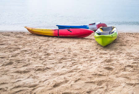 Three kayak boat on the sea shore leaving space at the bottom left Stock Photo