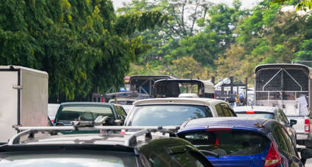 slow lane: Car queue in the bad traffic road contrast with the green trees Stock Photo