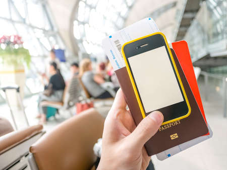 Hand holding passport, boarding pass and smart phone in airport in concept of going abroad