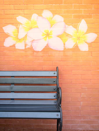 Black bench in front of flower painting alike processed brick wall Stock Photo - 60883257