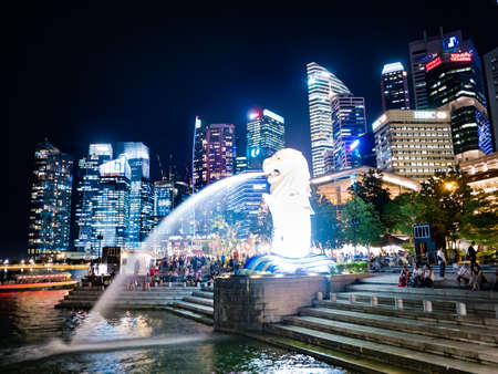 SINGAPORE - AUGUST 24, 2016 : The Merlion fountain in front of business buildings at night of Marina Bay in Singapore