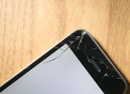 Corner cracked smartphone, screen turning on, isolated on wooden background