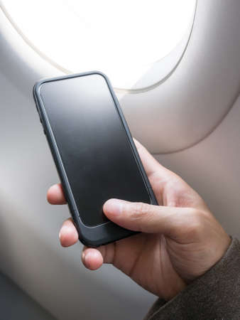 Hand holding blank and black cell phone beside an airplane window Stock Photo
