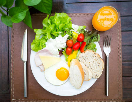 Healthy breakfast, salad, bread, ham, egg and orange juice on wooden table