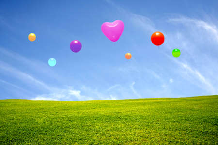 green meadow with blue sky and colorful balloons photo