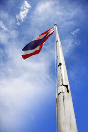 old flag of thailand holding up to beautiful blue sky with cloud