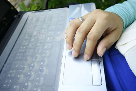 female hand control on a laptop touchpad photo