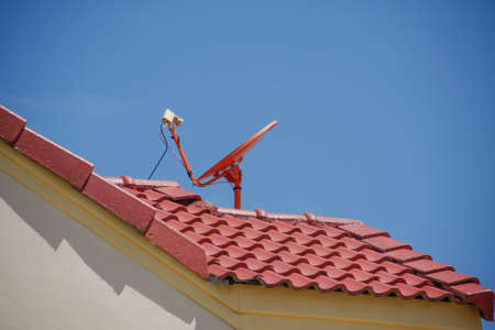 red roof with a satellite dish and blue sky photo