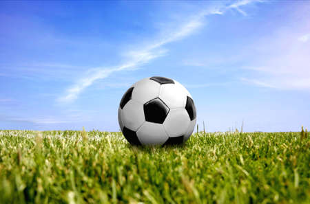 a ball on beautiful green grass with blue sky and cloud on background photo