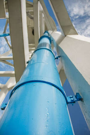 big blue pvc plumbing down from water tank with building structure Reklamní fotografie - 22447759