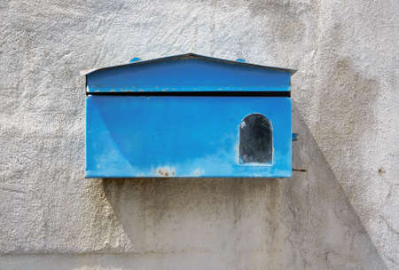blue mailbox front of old cement wall of home photo