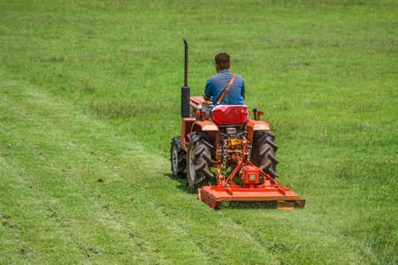 a man on mower cutting grass in football field Stock Photo