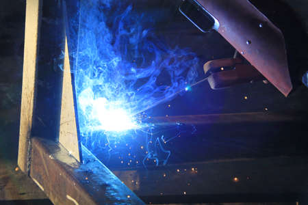 welding steel iron with blue smoke photo