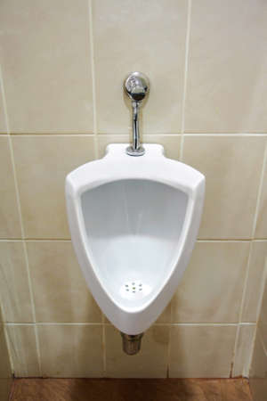 modern style white ceramic urinal in toilet for urine of men photo