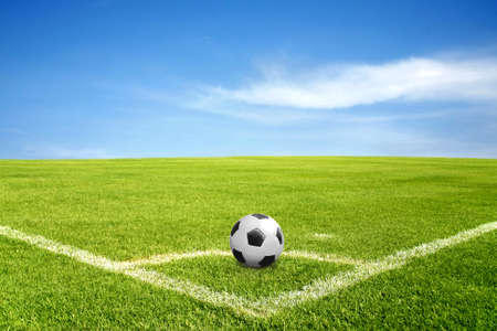 a ball on corner of football field in green grass with blue sky and cloud photo