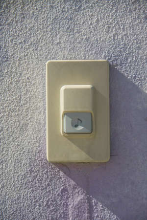 door bell on white gatepost front of house photo