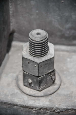 old dirty nuts with plate metal and protruding bolt for hold metal together and fix Stock Photo