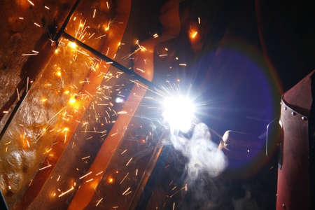 welding steel iron with lighting, smoke and sparks in night photo