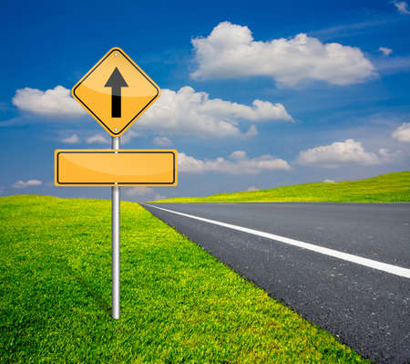 straight traffic sign with blank signs beside asphalt road and blue sky with green meadow photo