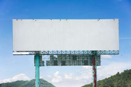 roadside billboard advertising display with blue sky and mountains photo