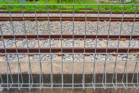 iron barred: net metal fence of railway tracks Stock Photo