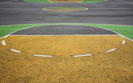 outdoor basketball court: old playground outdoor basketball court made of asphalt and painted in yellow with green Stock Photo