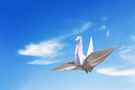 origami paper bird fly under blue sky, freedom concept Stock Photo