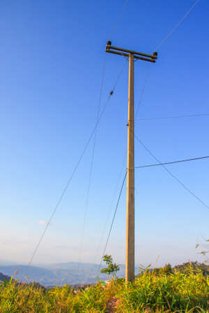 telegraphs: wire pole on mountain of countryside withe blue sky in afternoon Stock Photo