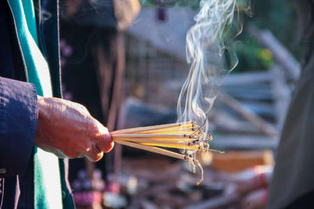 hand holding incense sticks for worship, praying god of Asia religion Banco de Imagens