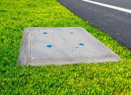 manhole cement beside asphalt road with green grass