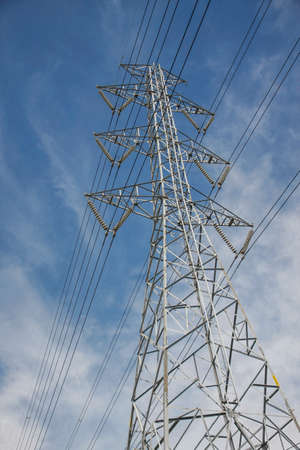 electric grid: high voltage pole construction with blue sky and cloud