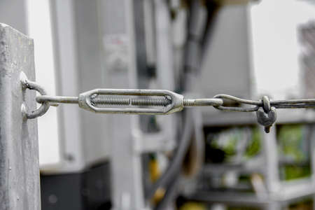 steel turnbuckle holding hook eye with fastening and metal cables Stock Photo