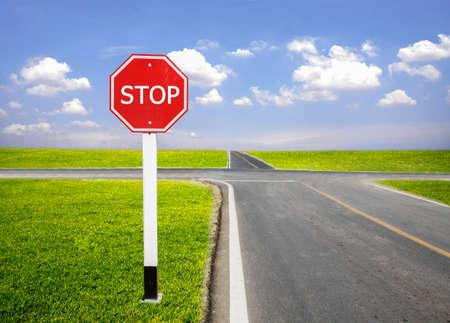 Fermi il palo del segnale stradale accanto alla strada della congiunzione con il campo verde e il cielo blu fresco nel giorno luminoso Archivio Fotografico - 83780259