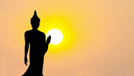 silhouette of buddha statue with sunset in evening, Phutthamonthon park Nakhonpathom, Thailand Stock Photo