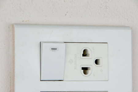 socket and switch on soft pink wall of room Stock Photo