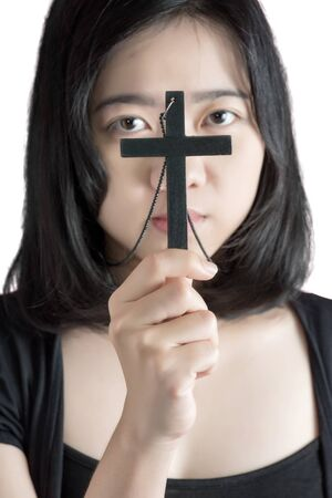 inscrutable: Beautiful asia woman with hopeful holding christian symbol of crucifix praying to God isolated on white background.