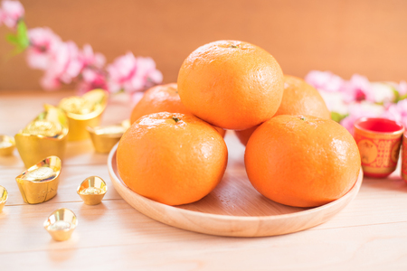 Top view accessories Chinese new year festival decorations.orange,leaf,wood dish,red packet,plum blossom, on wood background Stock Photo