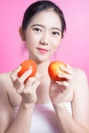 Asian woman with tomato concept. She smiling and holding tomato. Beauty face and natural makeup. Isolated over pink background