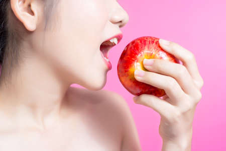 Asian woman with apple concept. She smiling and holding apple. Beauty face and natural makeup. Isolated over pink background Stock Photo