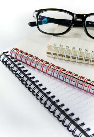 diary and glasses on white
